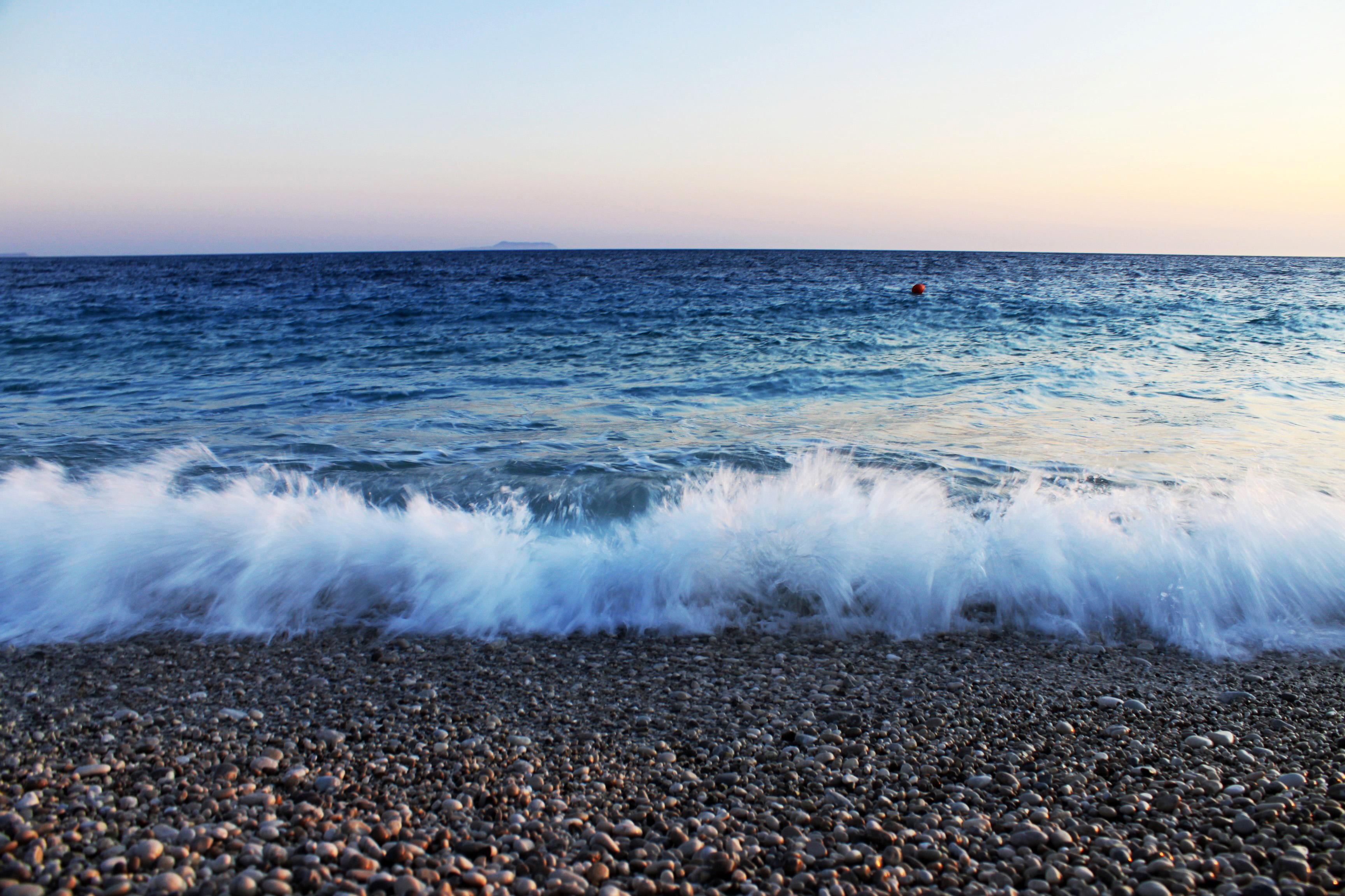 Waves crashing over pebbles on beach image - Free stock photo