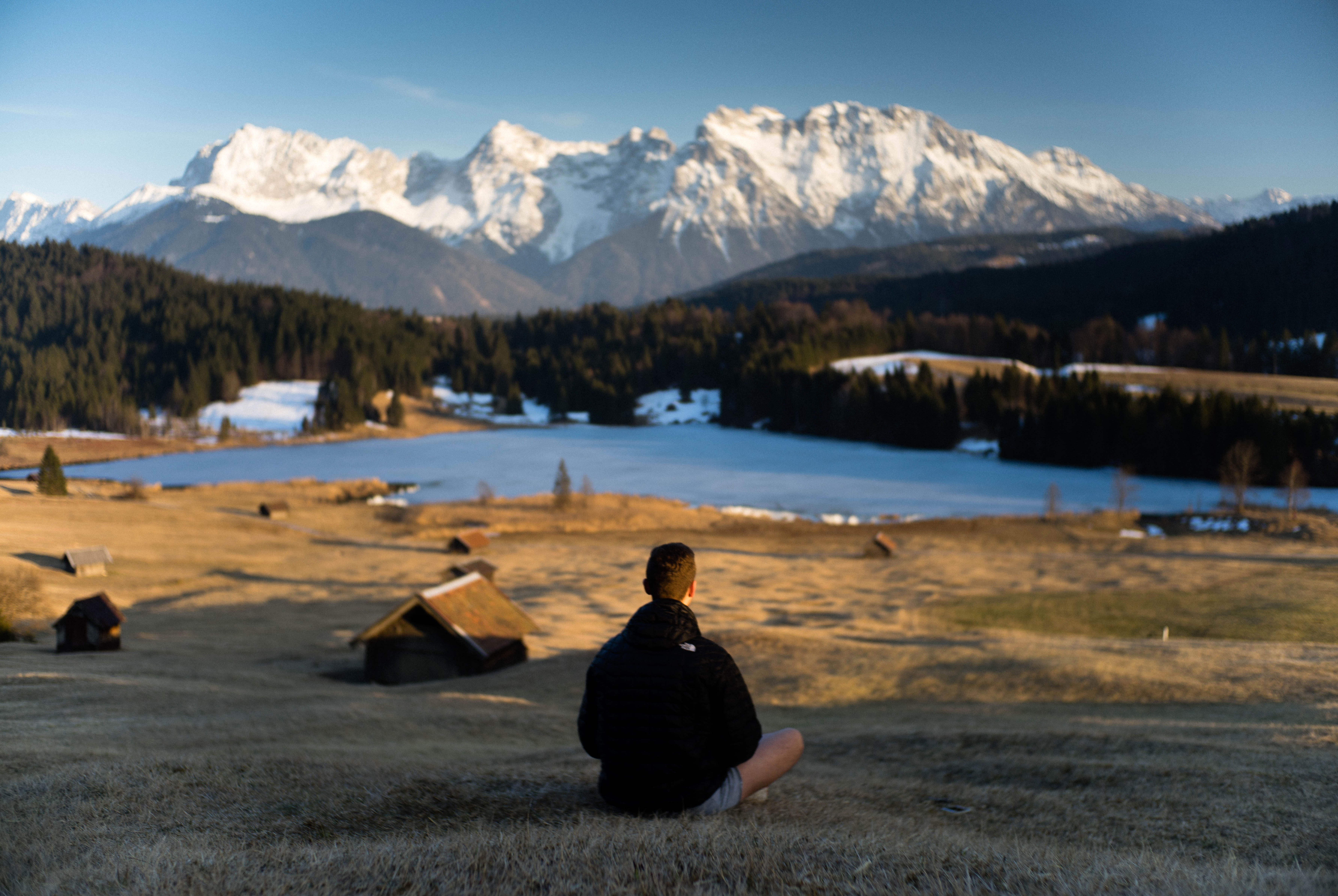 man looking at snow-capped mountains landscape in bavaria  germany image
