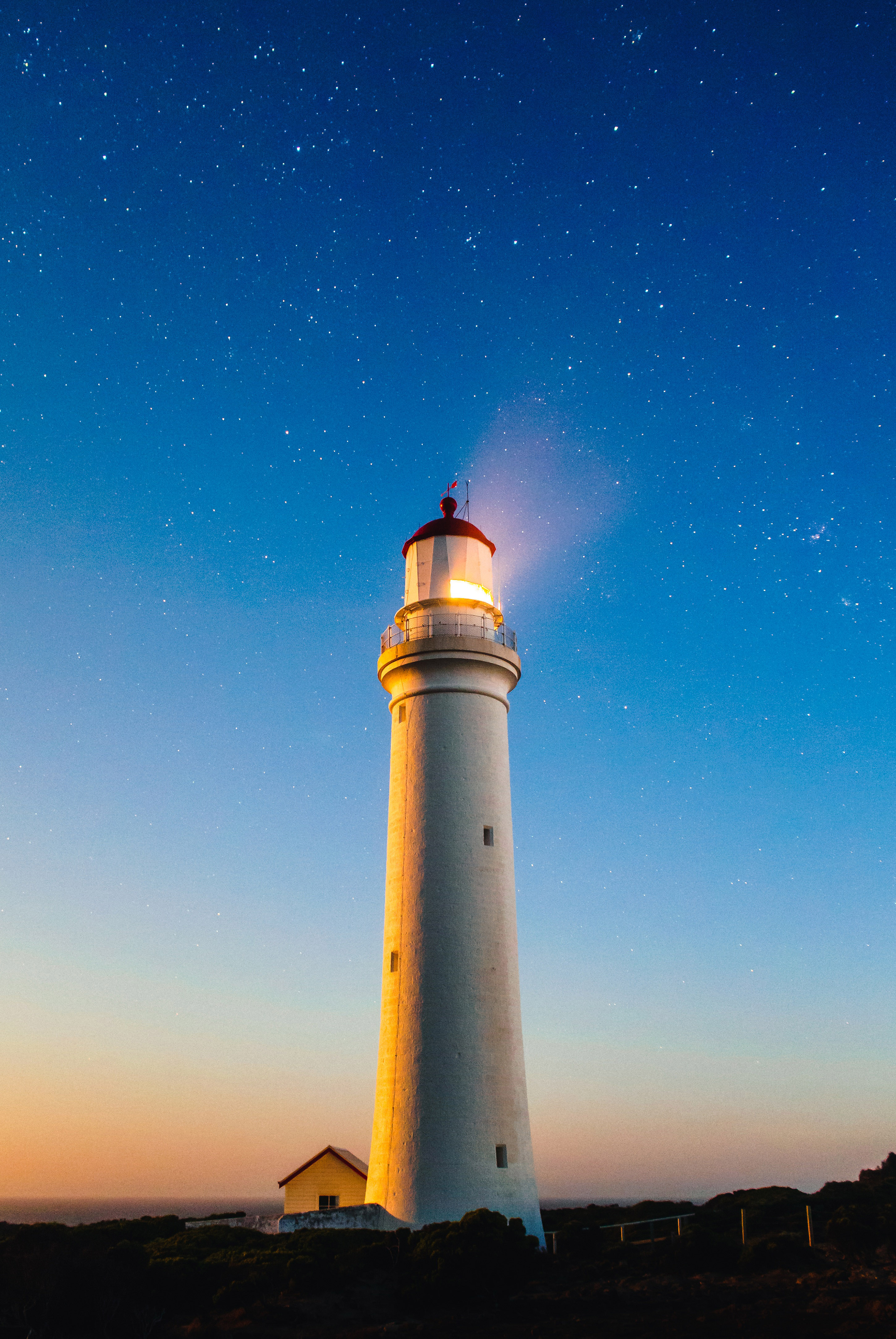 Lighthouse beneath the sky and stars with light on image ...