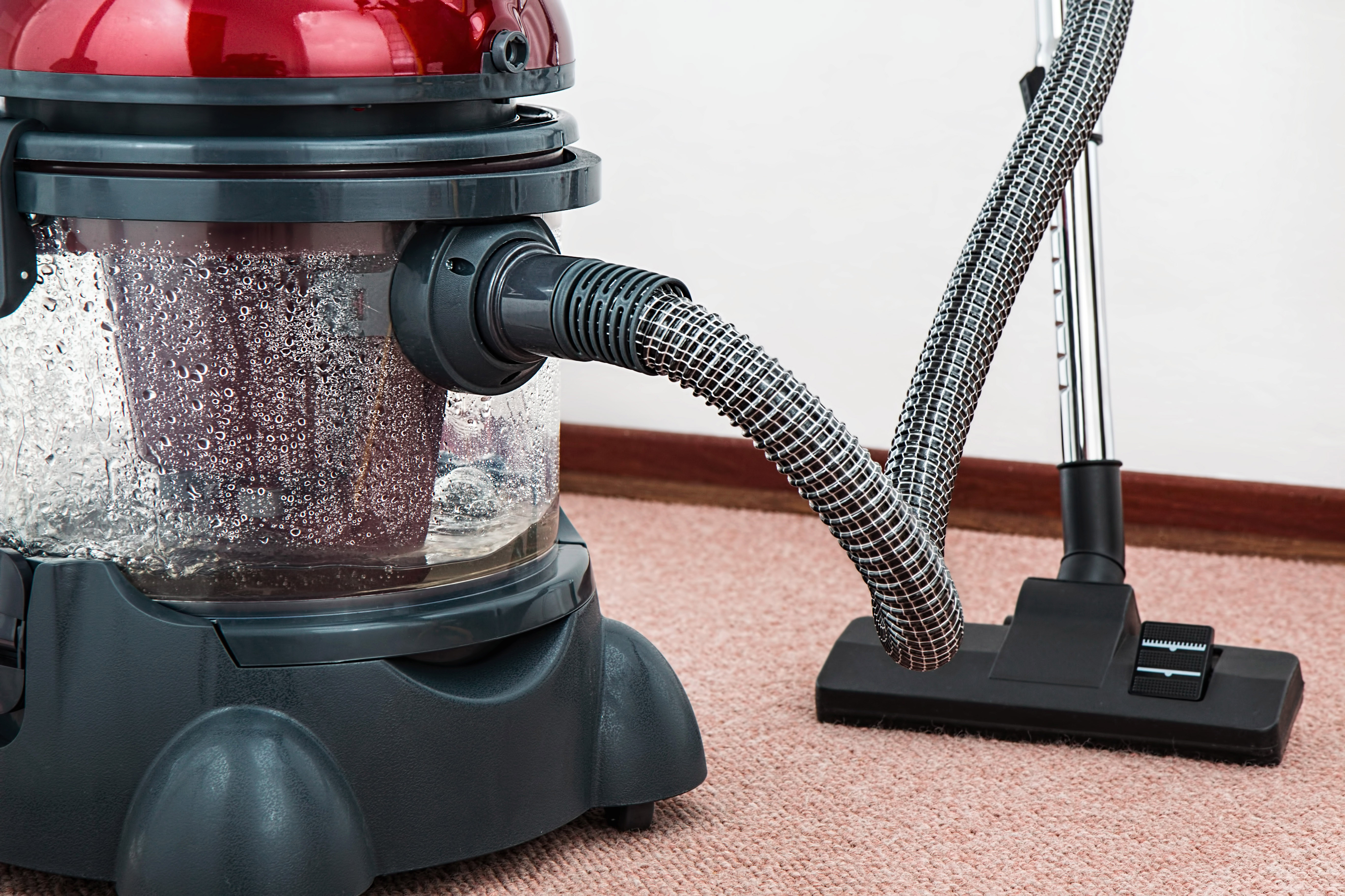 Red deep cleaner vacuum on carpet
