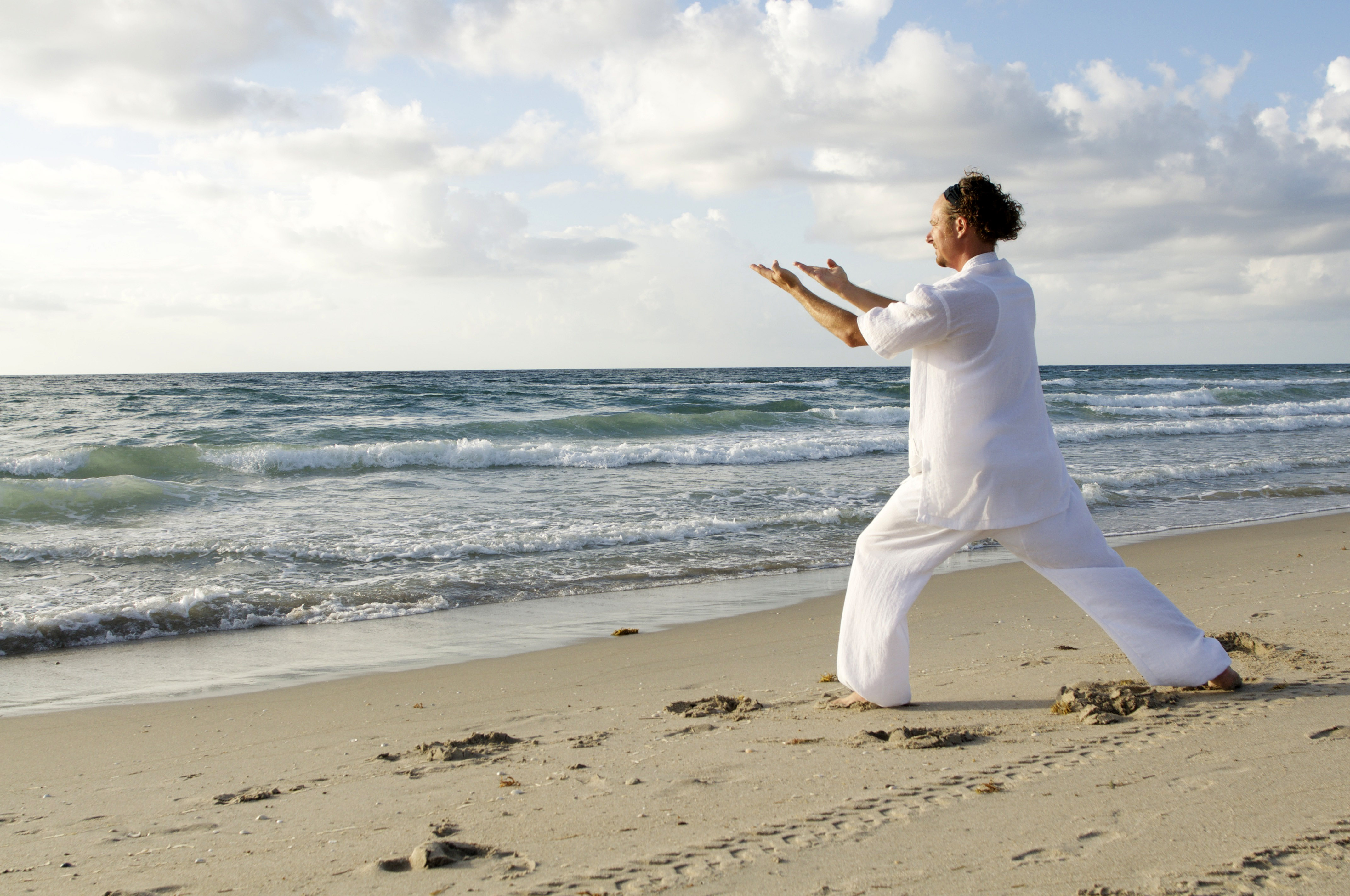 Man dressed in White Practicing Tai-Chi on the Beach image