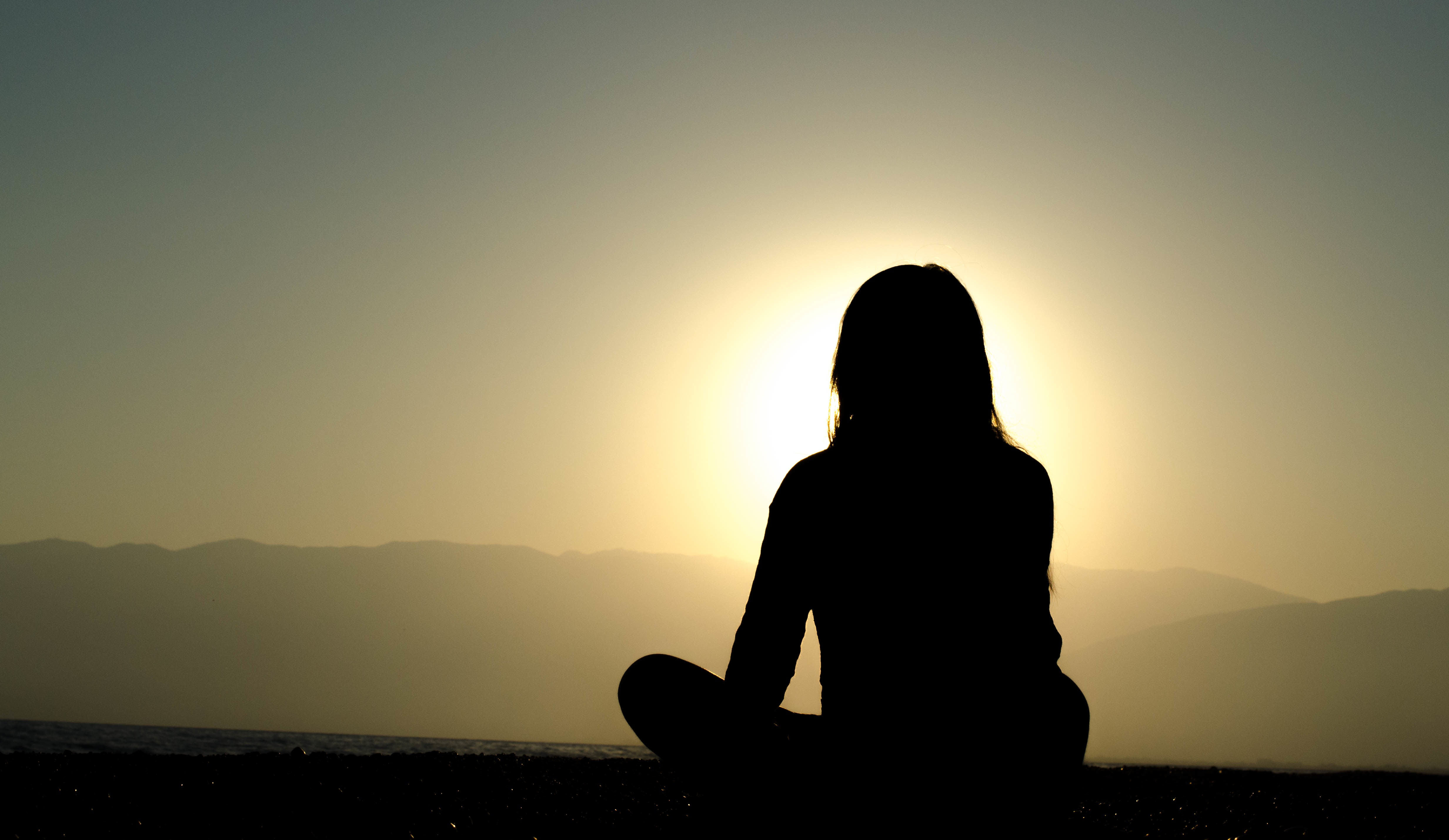 Outline of woman sitting on hill watching the sunset.