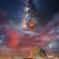 Galaxy and stars above the mountain with lightning