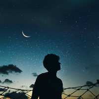 Silhouette of boy looking up at the sky of stars