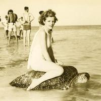 Young woman riding on the back of a turtle at Mon Repos Beach in Bundaberg, Queensland, Australia