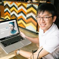 Asian Man smiling with a mockup on a macbook