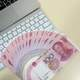 Macbook with a fan of chinese hundred dollar bills