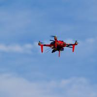 Red Drone Flying in the blue Sky