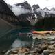 Canoes on Lake with Mountains in the scenic background in Banff National Park, Alberta, Canada