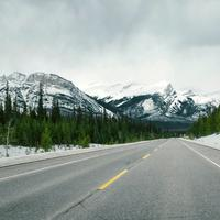 Road with snow-capped mountains with trees and landscape in Jasper National Park, Alberta, Canada