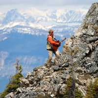 Man Climbing Rocky Mountain while playing Guitar