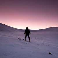 Purple Sunset in the winter of person hiking in the snow in Quebec, Canada