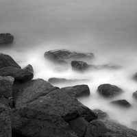 Mist and ocean waves splashing on rocks