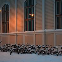 Snowy bicycles in front of library of architecture of Oulu University in Finland