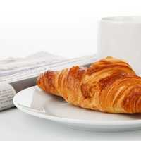 Croissant with tea and newspaper