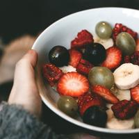 Hand holding a bowl of fruit