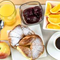 Hotel breakfast tray with oranges, coffee, and juice, and croissants
