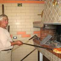 Man putting Pizza in the oven
