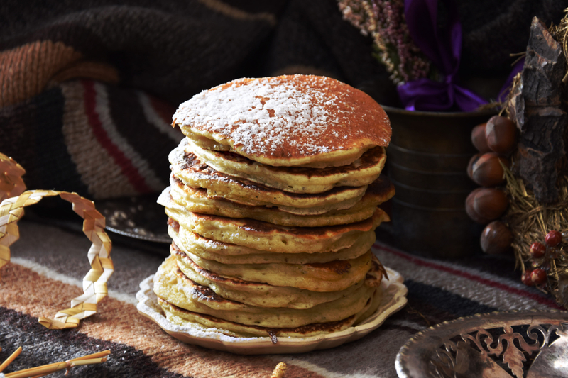 photo of a stack of pancakes with powdered sugar on top