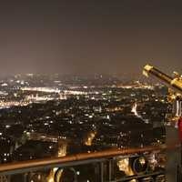 Kid in Paris looking through a telescope at night
