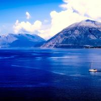 Sailboat on the ocean besides the mountains landscape shot in Greece