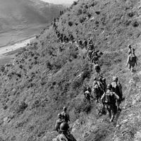 U.S. Marines move out over rugged mountain terrain during Korean War