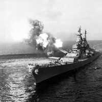 USS Missouri fires a salvo from its 16-inch guns at shore targets during Korean War