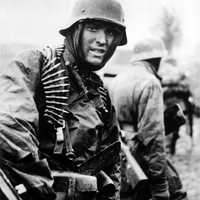 German machine gunner marching through the Ardennes in the Battle of the Bulge