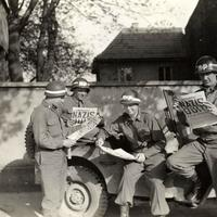 US military policemen read about the German surrender ending World War II in Europe