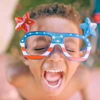 Kid Celebrating 4th of July with red white blue glasses
