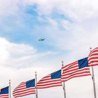 Plane flying above a bunch of USA Flags
