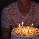 Person holding Birthday Cake with four candles