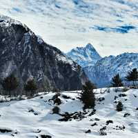 Snow-capped mountains with clouds overhead in Auli, India