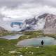 Male hiker in the Italian Dolomites Mountains overlooking a lake