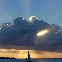 Sailboat under a clump of clouds at sunset in Jamaica