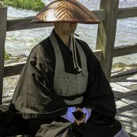 Monk waiting for offerings in Kyoto, Japan