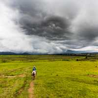 Plains landscape with storm clouds with horse rider