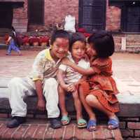Two kids hugging a smaller kid in Kathmandu, Nepal