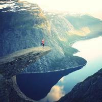 Women doing yoga overlooking the fjord in Trolltunga, Norway