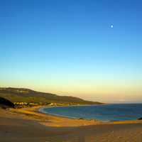 Beach landscape with moon in blue sky