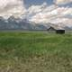 Beautiful Landscape with grassland and Mountains with Cabin under sky and clouds