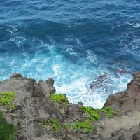 Blue Water Waves Crashing onto rocky shoreline