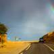 Car Driving into the landscape with a rainbow