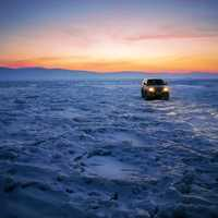 Car on frozen Lake Baikal with snow and ice