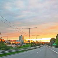 Highway and road into the sunset in town