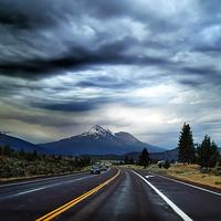 Highway Road into the mountains under heavy clouds