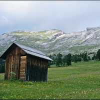 Lone Cabin on grassland by mountains