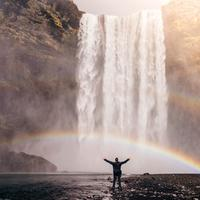 Man Standing Beneath the Waterfall and Double Rainbow