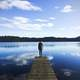 Man standing on the dock looking at the lake landscape