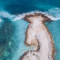 Ocean Waves crashing on small island aerial view